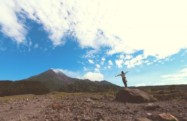 Woman alone on rock, with arms outstretched, feeling free