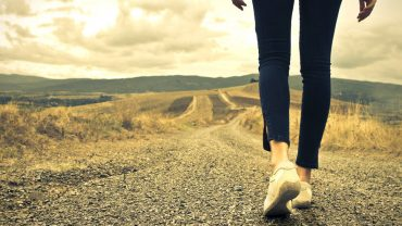 Woman walking alone on a gravel path