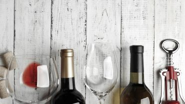 A series of wine glasses and unopened wine bottles
